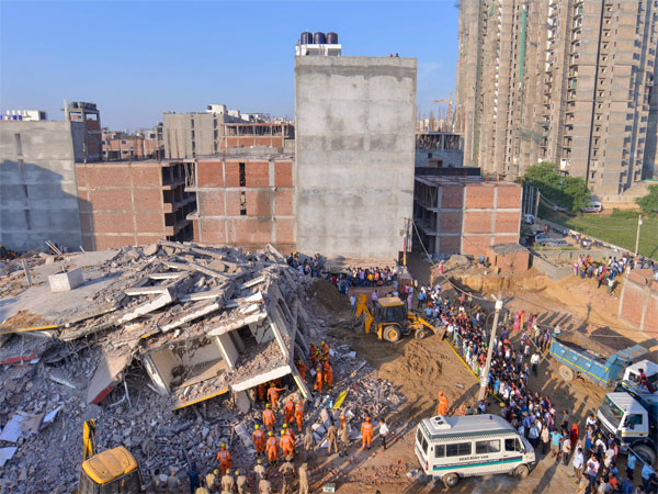 Rescue workers carry the body of a victim at the site of a collapsed building at Shahberi village, in Greater Noida West