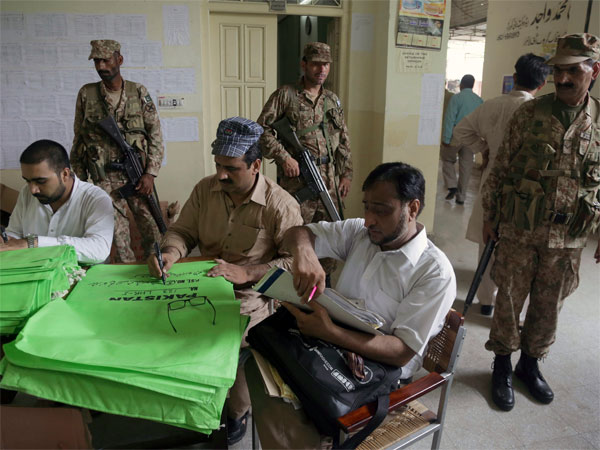 Pakistani troops stand guard while Pakistans Election Commission staff preparing election material for upcoming general election at an office in Lahore, Pakistan