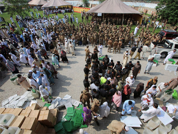 Election staff gather at a distribution center to receive polling material for elections, in Peshawar, Pakistan