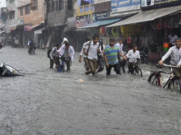 Pedestrians try to cross a flooded road during rainfall, in Meerut on Friday, 27 July 2018.