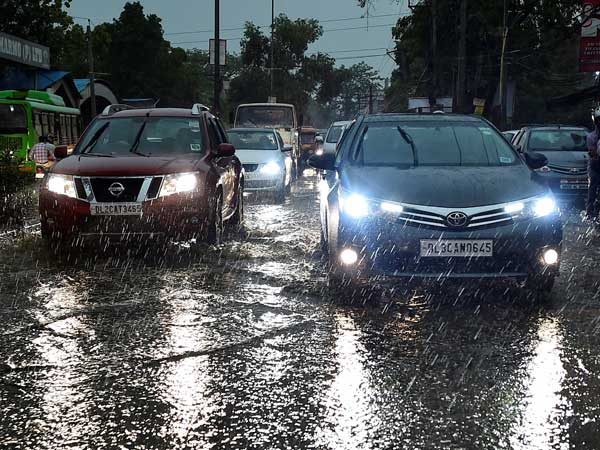 Vehicles ply at a road as it rains in New Delhi