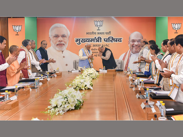 Prime Minister Narendra Modi being welcomed by BJP president Amit Shah as other leaders clap, during a day-long meeting of the BJP Chief Ministers Council in New Delhi