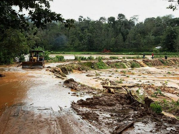 An earth-mover clears the sludge from a road in the flood-hit Madapur village of Kadagu district, Karnataka on Tuesday, Aug 21, 2018. (PTI Photo)
