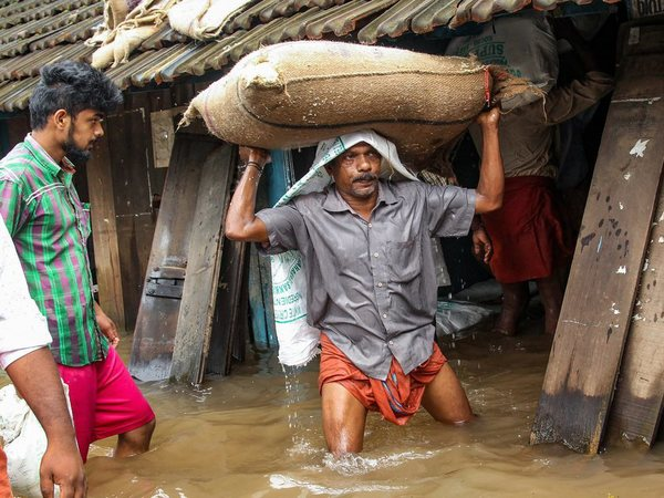 A person carries a grain sack as his house gets flooded after Kakkayam dam was opened following heavy monsoon rainfall, in Kozhikode. PTI file photo