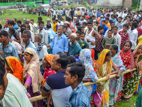 People wait to check their names on the final draft of the states National Register of Citizens after it was released, at an NRC Seva Kendra
