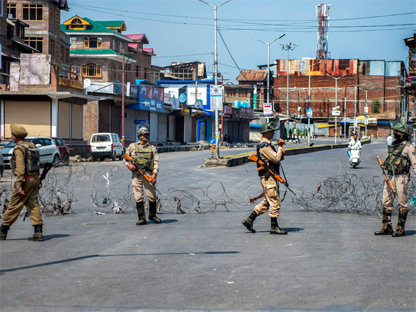 Security personnel stand guard along a barbed wire during a strike called by separatist leaders against the recent civilian and militant killings in south Kashmir, in Srinagar