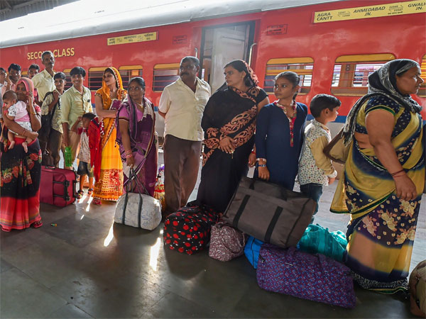 Migrant workers wait to board a train out of Gujarat