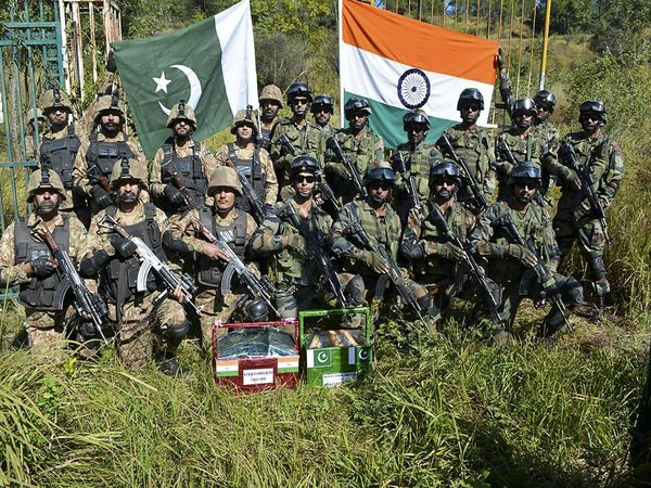Indian and Pakistani army men pose for a group photograph after exchanging sweets in Poonch