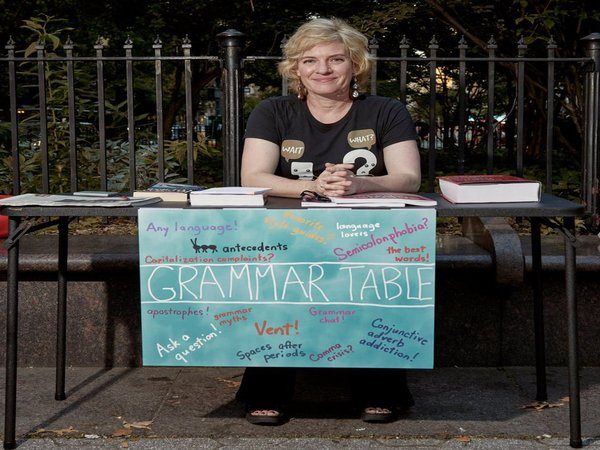 She sits on the road side to clear people's grammar confusion & also serve a greater purpose
