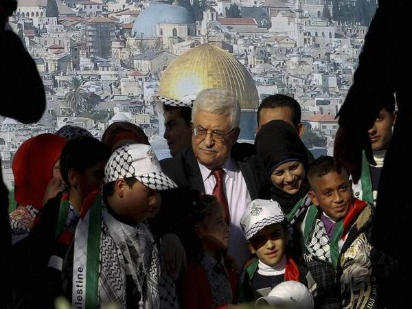Palestinian President Mahmoud Abbas, center, is surrounded by children in the West Bank city of Ramallah. PTI file photo