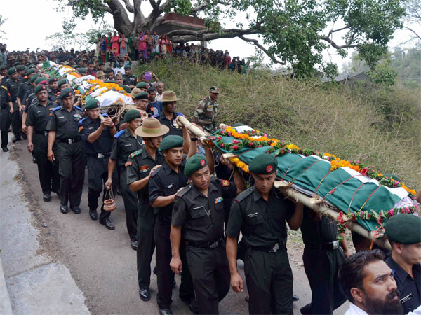Soliders carry mortal remains of martyred soldiers