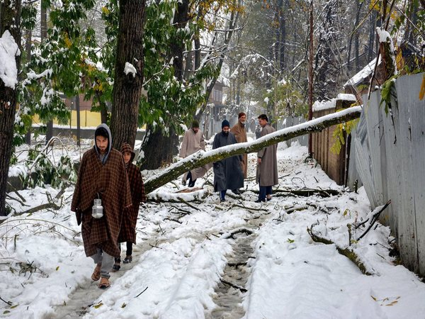 People walk on a snow covered road after heavy snowfall in Anantnag