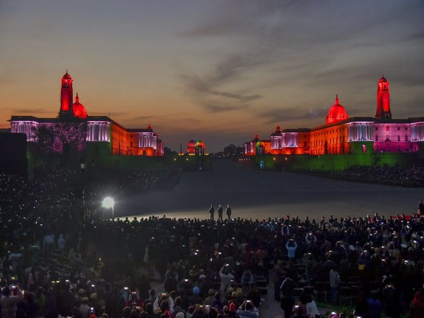 Members of the audience wave their mobile phones to add light to the illuminated Raisina Hills