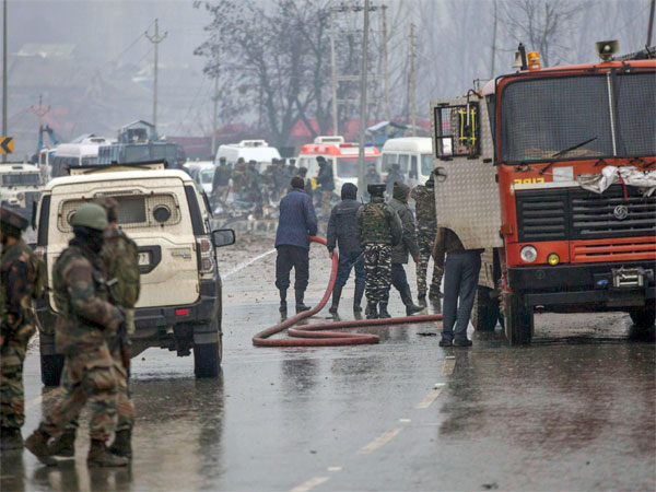 Firemen spray water on a road to wash away the blood stains at the site of suicide bomb attack at Lathepora Awantipora in Pulwama district of south Kashmir