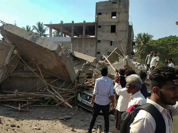Rescue officials and locals carry out search and rescue operation after a multistorey building collapsed in Dharwad, Karnataka