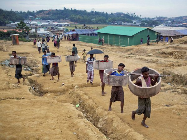 Rohingya Muslims, who crossed over from Myanmar into Bangladesh, carrying construction material and walk towards Jamtoli refugee camp in Ukhiya, Bangladesh, Friday, Nov. 17, 2017. PTI file photo