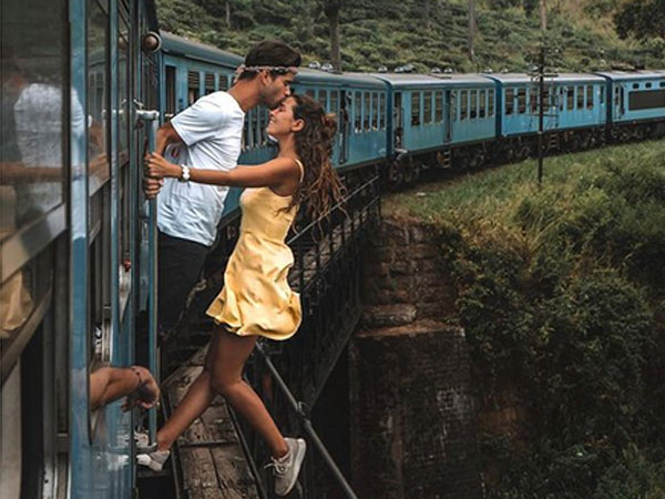 Portuguese traveller couple takes romantic photo hanging outside train