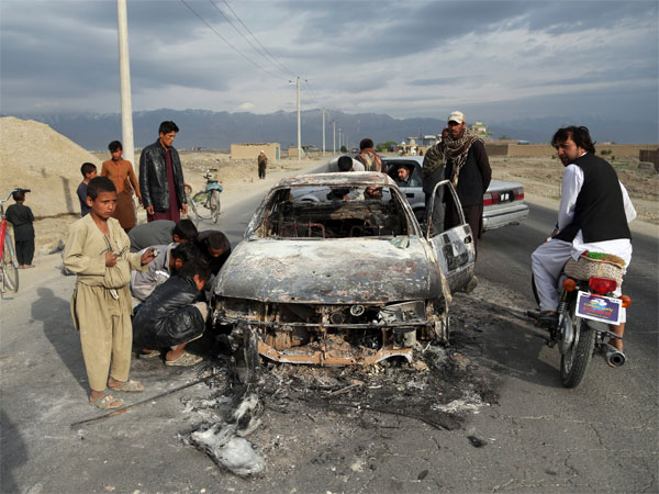 Afghans watch a civilian vehicle burnt after being shot by US forces after an attack near the Bagram Air Base, north of Kabul, Afghanistan, Tuesday, April 9, 2019. Three American service members and a U.S. contractor were killed when their convoy hit a roadside bomb on Monday near the main U.S. base in Afghanistan, the U.S. forces said. The Taliban claimed responsibility for the attack. AP/PTI