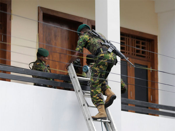 A Sri Lankan police commando enters a house suspected to be a hideout of militants following a shoot out in Colombo, Sri Lanka