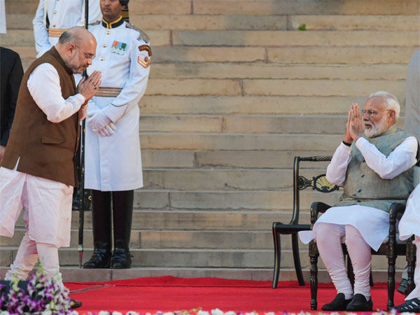 Amit Shah exchanges greetings with Prime Minister Narendra Modi after he took oath as a Cabinet minister during a swearing-in ceremony at the forecourt of Rashtrapati Bhawan in New Delhi