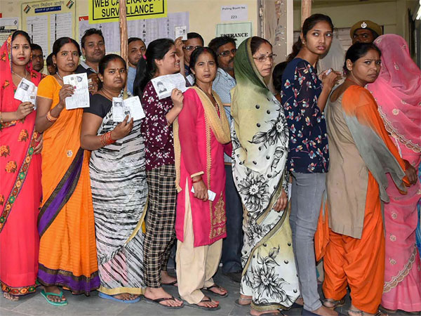 Voters stand in queues at a polling booth during the 6th phase of Lok Sabha elections 2019, at Badarpur in Delhi