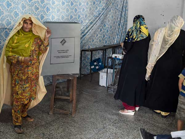 Muslim women leave after casting votes at a polling booth
