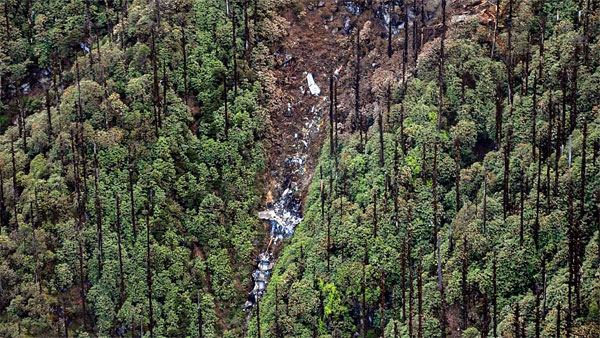 In this photo released by Indian Air Force, is seen the crash site from where the mortal remains and other material evidences are being picked up in respect to the crash of IAF AN-32 carrier aircraft, that took off from Air Force Station