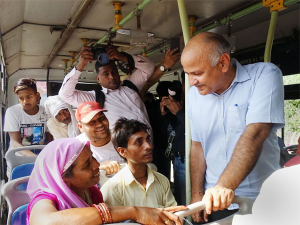 Delhi Deputy Chief Minister Manish Sisodia interacts with a woman passenger in a DTC bus, in New Delhi