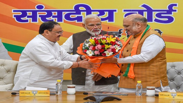 BJP President Amit Shah gives a bouquet to JP Nadda after he was appointed as BJP Working President