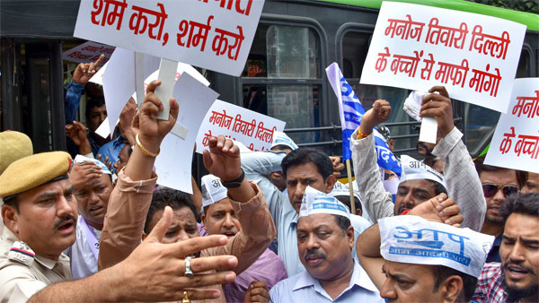 Aam Admi Party supporters hold banners as they protest at Delhi BJP president Manoj Tiwaris residence over false allegation on Delhi Deputy Chief Minister Manish Sisodia in New Delhi