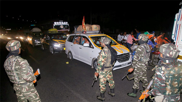 Security personnel stand guard as a convoy carrying the first batch of Amarnath pilgrims leave for yatra from Jammu