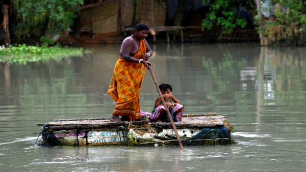 A Villager usees a raft in flood-affected area in Assam. PTI file photo