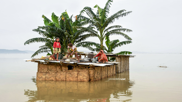 A family marooned on the top of a hut in the flood-hit locality