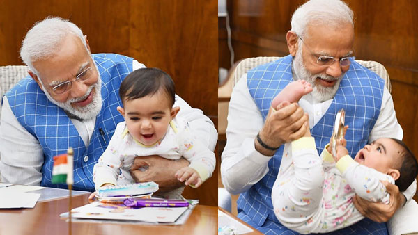 Prime Minister Narendra Modi plays with a child at Parliament, in New Delhi
