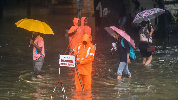 A Municipal worker stands guard to warn pedestrians of an open manhole on a waterlogged street following heavy monsoon rains, in Mumbai