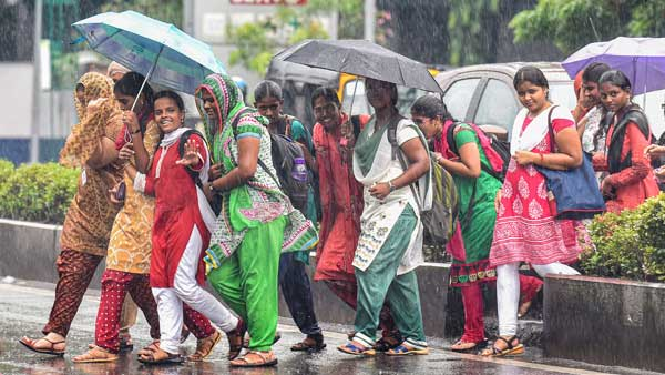 College students cross a road amid rains