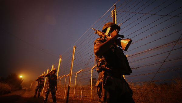 Border Security Force (BSF) soldiers patrol near International border on the outskirts of Jammu