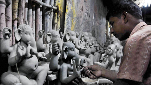 An artist making clay idol of Lord Ganesha for the upcoming Ganesh Chaturthi festival