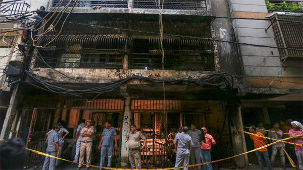 People look at the charred remains of a building where a massive fire broke out, at Zakir Nagar area, in New Delhi