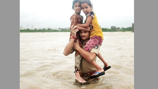 Gujarat cop carries two girls on his shoulder as he wades through gushing waters