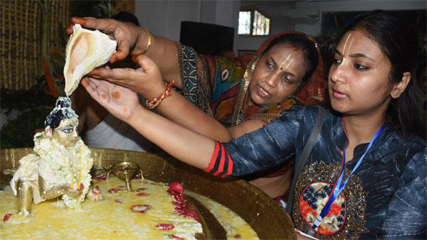 Devotees perform abhishek of Lord Krishna on the occasion of Krishna Janmashtami