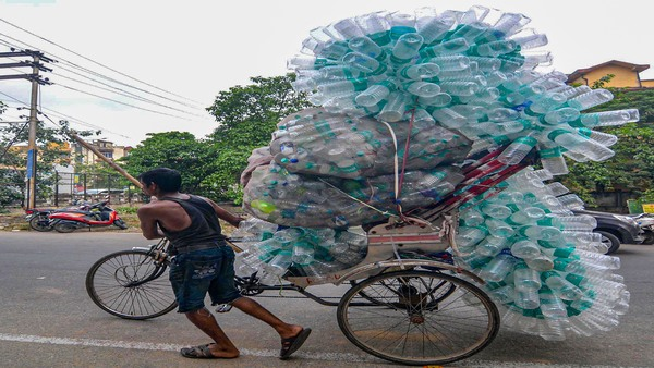 A rickshaw puller carrying empty plastic bottles to a recycling centre