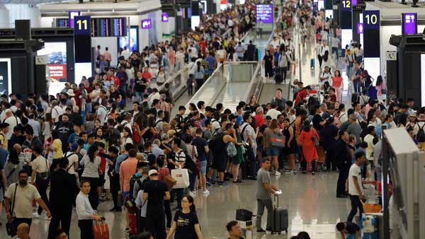 Travelers crowd at the departure hall of the Hong Kong International Airport