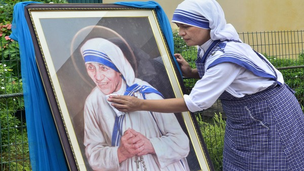 Agartala: Catholic nun cleans a portrait of late Mother Teresa on her 109rd birth anniversary, at an orphanage at Agartala, on Saturday. (Image - PTI)