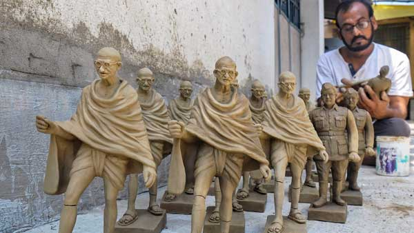 An artist gives finishing touch to clay sculptures of Mahatma Gandhi