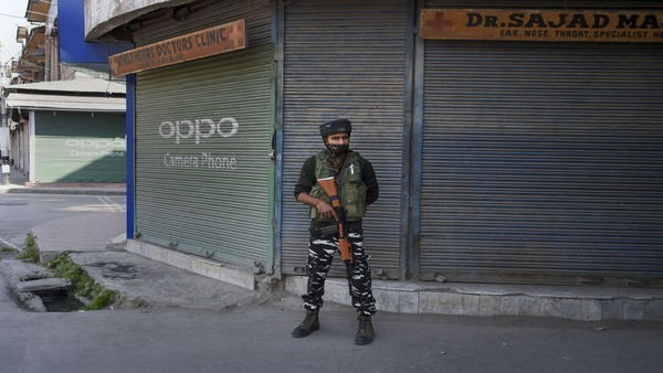 A security personnel stands guard outside closed shops during shutdown in Srinagar
