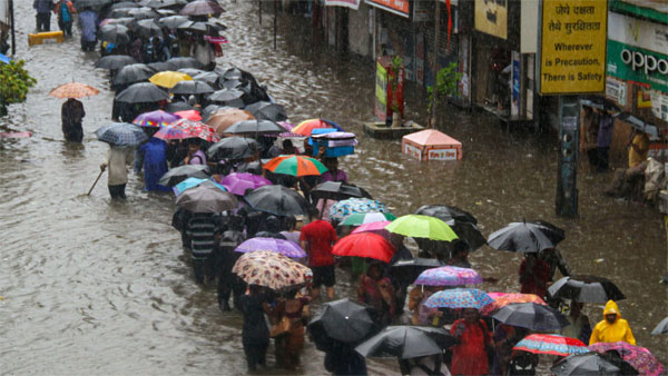 People wade through a flooded street during heavy rain, in Mumbai