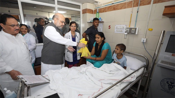 Home Minister Amit Shah distributing food to a patient at AIIMS