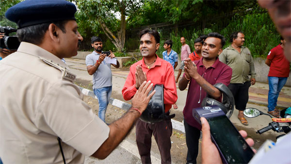 Traffic offenders request policemen after violating traffic rules, at Ring Road in New Delhi