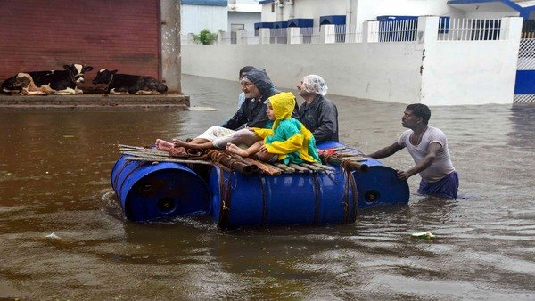 Peoples sit on a makeshift boat to cross the flood-affected area of Sakha Maidan following heavy monsoon rainfall in Patna